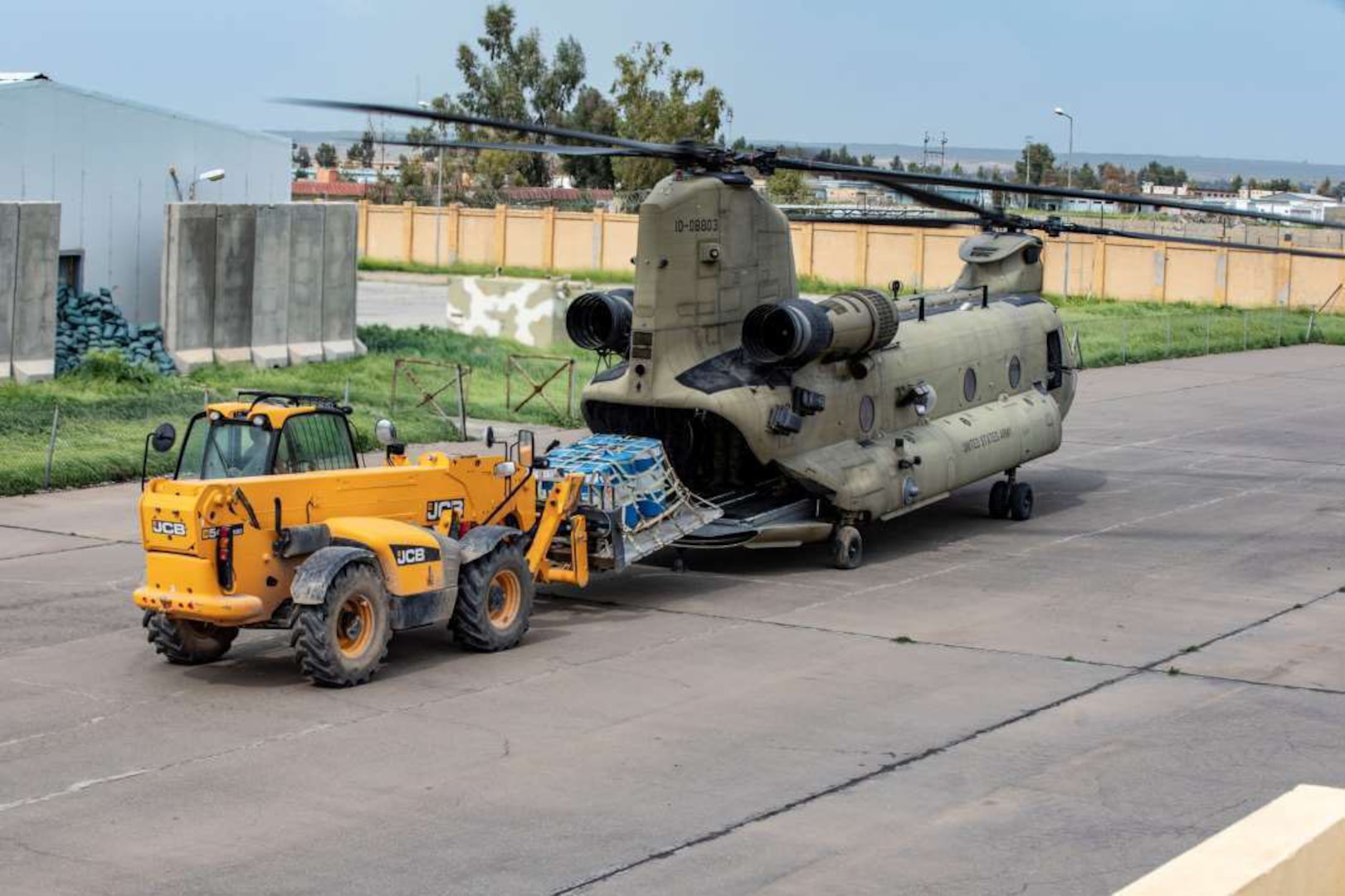 A small vehicle loads a pallet onto a helicopter.