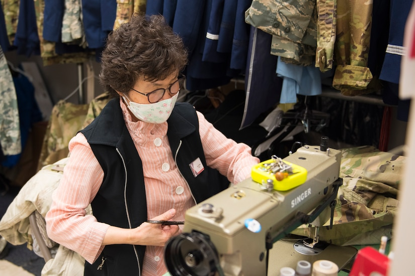 Kum Sun Yun, the manager of Stripes Alterations Shop, alters a uniform top at Joint Base Charleston, S.C., April 7, 2020. Employees at Stripes Alterations Shop are taking safety precautions such as wearing masks, cleaning work areas and washing their hands frequently. The hours of operation for alterations are from 9 a.m. to 5 p.m. Monday through Friday and 9 a.m. to 3 p.m. on Saturdays.