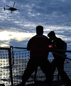 Sailors lower safety nets on the flight deck of USS Pinckney April 14, 2020.