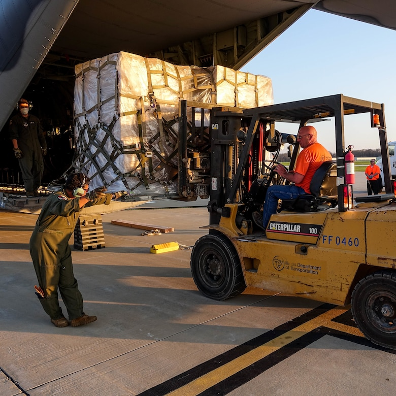 A forklift operator prepares to offload a military cargo plane.