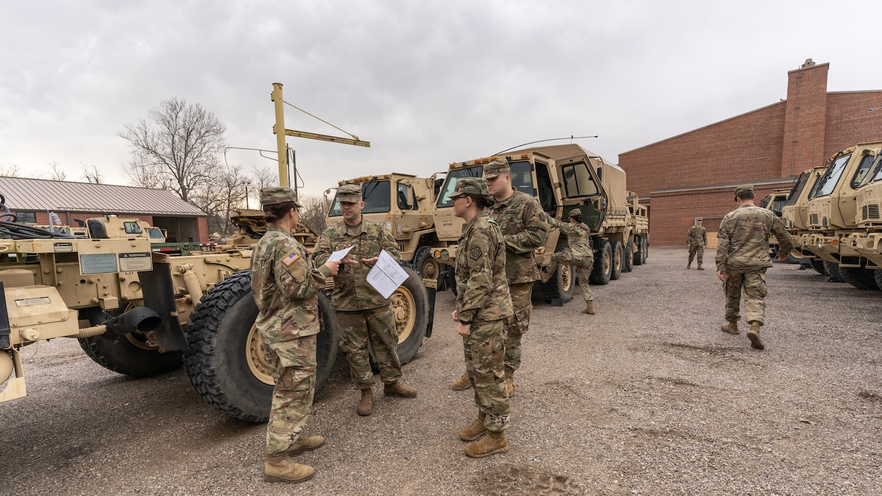 A small group of four troops discuss logistics while other troops board military vehicles in the background.