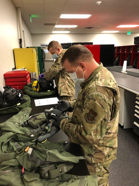 Tech. Sgt. William Vass and Tech. Sgt. Corey Johnson from the Aircrew Flight Equipment shop in the 419th Operations Support Squadron conduct quality control inspections on pilot flight gear.