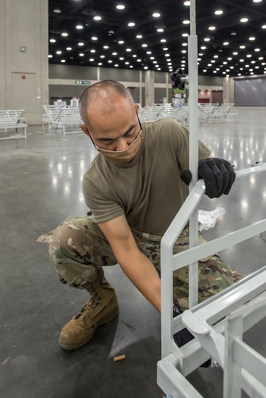 Master Sgt. Bao Huyng of the Kentucky Air National Guard's 123rd Airlift Wing sets up hospital beds at the Kentucky Fair and Exposition Center in Louisville, Ky., April 11, 2020. The site, which is expected to be operational April 15, will serve as an Alternate Care Facility for patients suffering from COVID-19 if area hospitals exceed available capacity. The facility initially can treat up to 288 patients and is scalable to 2,000 beds. (U.S. Air National Guard photo by Dale Greer)