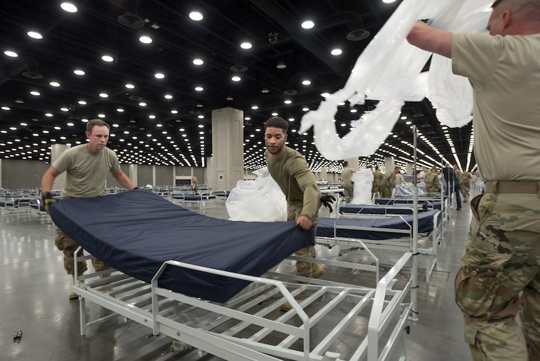 Staff Sgt. Wesley Hack (left) and Senior Airman Trenton Curry (center) of the Kentucky Air National Guard's 123rd Civil Engineer Squadron place a mattress on a hospital bed at the Kentucky Fair and Exposition Center in Louisville, Ky., April 11, 2020. The site, which is expected to be operational April 15, will serve as an Alternate Care Facility for patients suffering from COVID-19 if area hospitals exceed available capacity. The location initially can treat up to 288 patients and is scalable to 2,000 beds. (U.S. Air National Guard photo by Dale Greer)