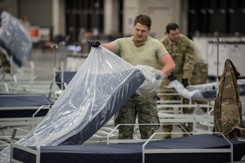Airman 1st Class Steve Shaffer of the Kentucky Air National Guard's 123rd Airlift Wing places a mattress on a hospital bed at the Kentucky Fair and Exposition Center in Louisville, Ky., April 11, 2020. The site, which is expected to be operational April 15, will serve as an Alternate Care Facility for patients suffering from COVID-19 if area hospitals exceed available capacity. The location initially can treat up to 288 patients and is scalable to 2,000 beds. (U.S. Air National Guard photo by Dale Greer)