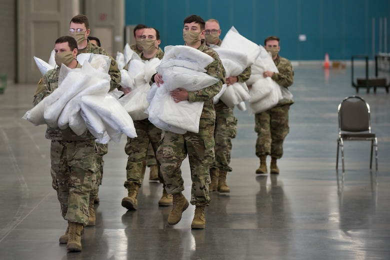 Soldiers from the Kentucky Army National Guard's 103rd Chemical Battalion distribute hospital bed pillows for an Alternate Care Facility at the Kentucky Fair and Exposition Center in Louisville, Ky., April 14, 2020. The site, which is expected to be operational April 15, will treat patients suffering from COVID-19 if area hospitals exceed available capacity. The location initially will offer care for up to 288 patients and is scalable to 2,000 beds. (U.S. Air National Guard photo by Dale Greer)