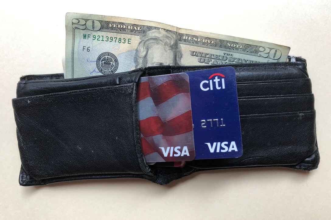 A photograph shows a wallet with money and credit cards sticking out.