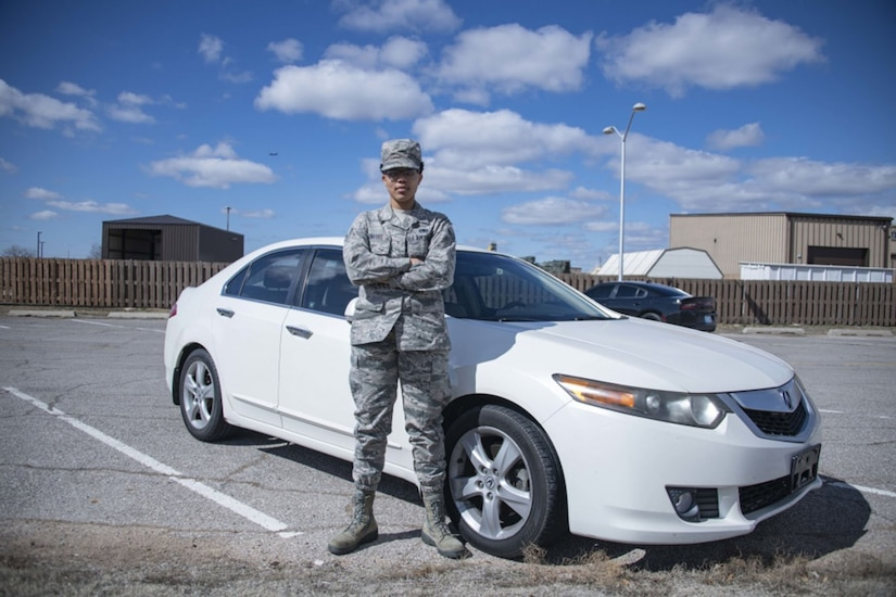A woman in a military uniform stands in front of a car.