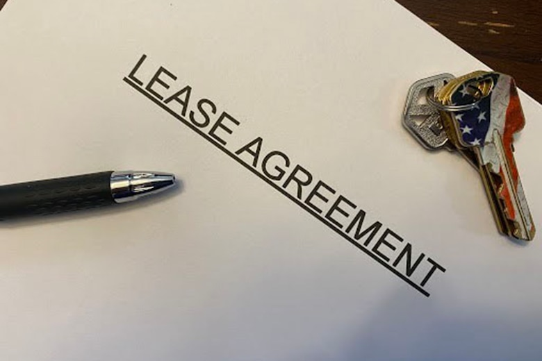 A photograph shows two keys, a pen and a paper with the words lease agreement.