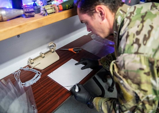Senior Airman Jace Zook marks where to cut a piece of plastic.