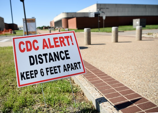 A Center of Disease Control sign stakes into the ground near the Di Tommaso Hall on Goodfellow Air Force Base, Texas, April 13, 2020.  Signs were placed around the base reminding personnel to maintain a social distance of at least six feet to limit the spread of COVID-19. The 17th Training Wing Commander declared Goodfellow a public health emergency and limited base access to mission essential personnel.  (U.S. Air Force Airman 1st Class Abbey Rieves)