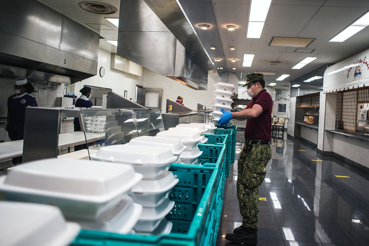 A sailor holds a stack of food containers while standing by crates filled with other containers in a cafeteria kitchen.