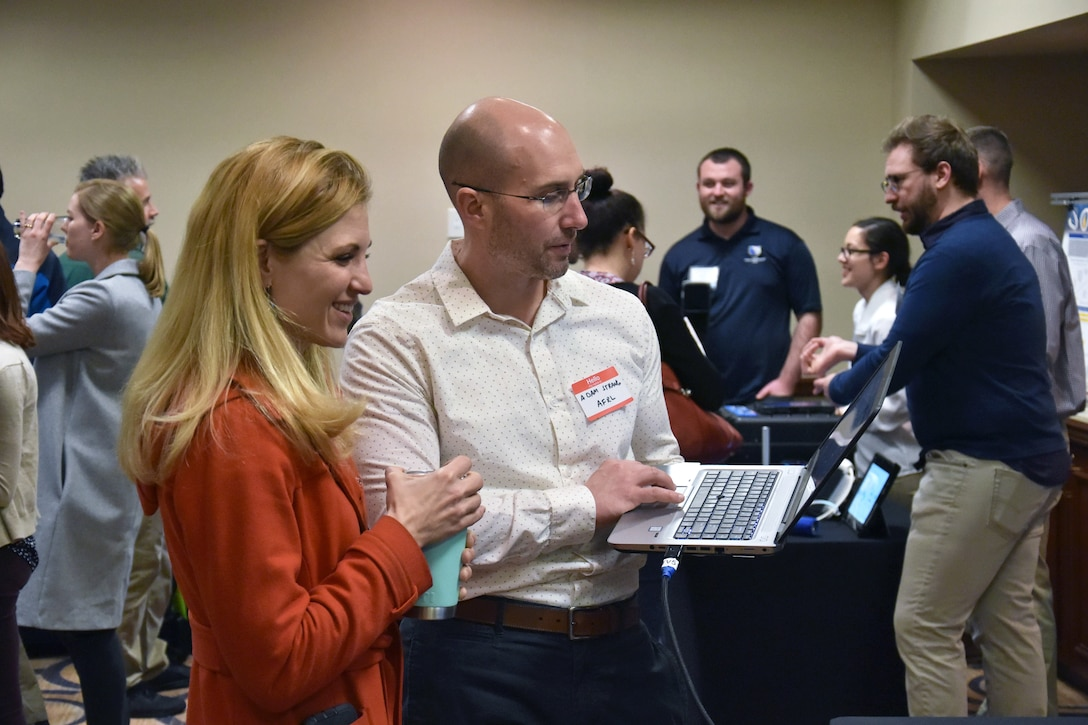 Dr. Adam Strang demonstrates Airman Data Analysis and Performance Tracking System to Dr. Jill McQuade, one of the Biotech Days organizers. Both are from the 711th Human Performance Wing. (U.S. Air Force photo/Spencer Deer)