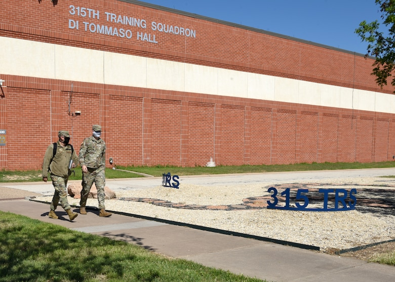 U.S. Air Force Airmen from the 315th Training Squadron, wear masks while leaving Di Tommaso Hall on Goodfellow Air Force Base, Texas, 2020. Goodfellow members were directed under the Department of Defense to wear cloth face coverings when members couldn't maintain six feet of social distance in public areas or work centers during the COVID-19 pandemic.  The DoD implemented necessary measures to mitigate the spread of the disease and safeguard national security capabilities. (U.S. Air Force Airman 1st Class Abbey Rieves)