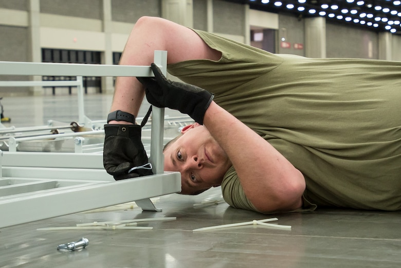 Tech. Sgt. Brandon Hall of the Kentucky Air National Guard's 123rd Civil Engineer Squadron sets up hospital beds at the Kentucky Fair and Exposition Center in Louisville, Ky., April 11, 2020. The site, which is expected to be operational April 15, will serve as an Alternate Care Facility for patients suffering from COVID-19 if area hospitals exceed available capacity. The location initially can treat up to 288 patients and is scalable to 2,000 beds. (U.S. Air National Guard photo by Dale Greer)