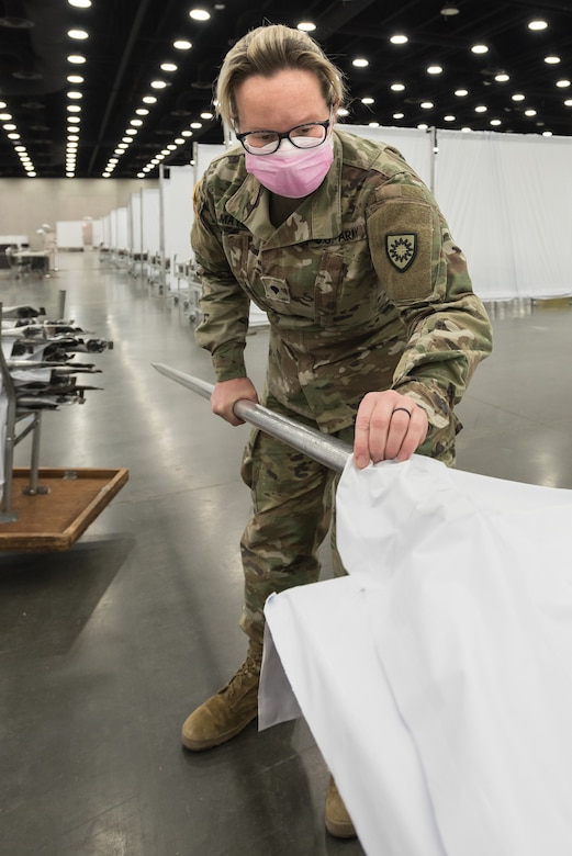 Spc. Samantha Mays of the Kentucky Army National Guard's 103rd Chemical Battalion sets up vinyl partitions to go between hospital beds at the Kentucky Fair and Exposition Center in Louisville, Ky., April 14, 2020. The site, which is expected to be operational April 15, will serve as an Alternate Care Facility for patients suffering from COVID-19 if area hospitals exceed available capacity. The location initially can treat up to 288 patients and is scalable to 2,000 beds. (U.S. Air National Guard photo by Dale Greer)