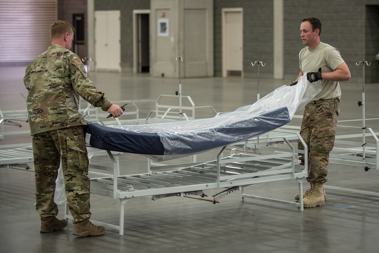 Capt. Jason Selby (left) and Staff Sgt. Wesley Hack of the Kentucky Air National Guard's 123rd Civil Engineer Squadron place a mattress on a hospital bed at the Kentucky Fair and Exposition Center in Louisville, Ky., April 11, 2020. The site, which is expected to be operational April 15, will serve as an Alternate Care Facility for patients suffering from COVID-19 if area hospitals exceed available capacity. The location initially can treat up to 288 patients and is scalable to 2,000 beds. (U.S. Air National Guard photo by Dale Greer)