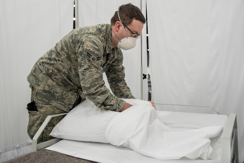 Airman 1st Class Trevor Johnson of the Kentucky Air National Guard's 123rd Civil Engineer Squadron cases pillows for an Alternate Care Facility at the Kentucky Fair and Exposition Center in Louisville, Ky., April 14, 2020. The site, which is expected to be operational April 15, will treat patients suffering from COVID-19 if area hospitals exceed available capacity. The location initially will offer care for up to 288 patients and is scalable to 2,000 beds. (U.S. Air National Guard photo by Dale Greer)