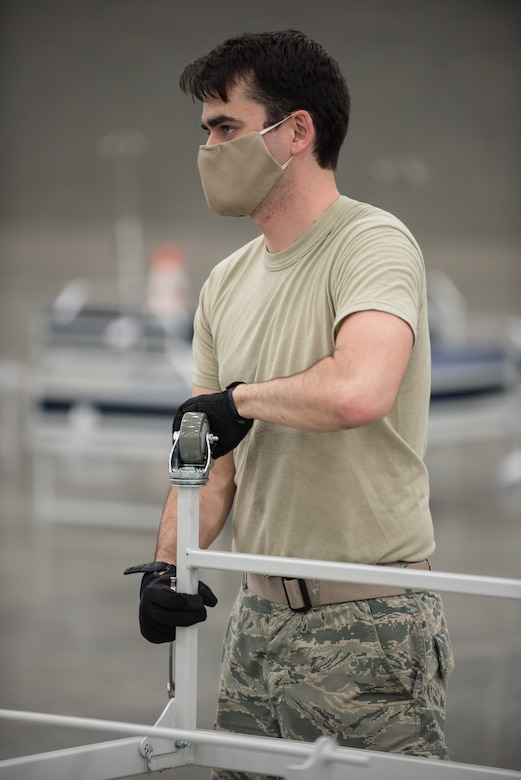 Airman 1st Class Tristan Baxter of the Kentucky Air National Guard's 123rd Civil Engineer Squadron sets up hospital beds and clinical space at the Kentucky Fair and Exposition Center in Louisville, Ky., April 13, 2020. The site, which is expected to be operational April 15, will serve as an Alternate Care Facility for patients suffering from COVID-19 if area hospitals exceed available capacity. The location initially can treat up to 288 patients and is scalable to 2,000 beds. (U.S. Air National Guard photo by Dale Greer)