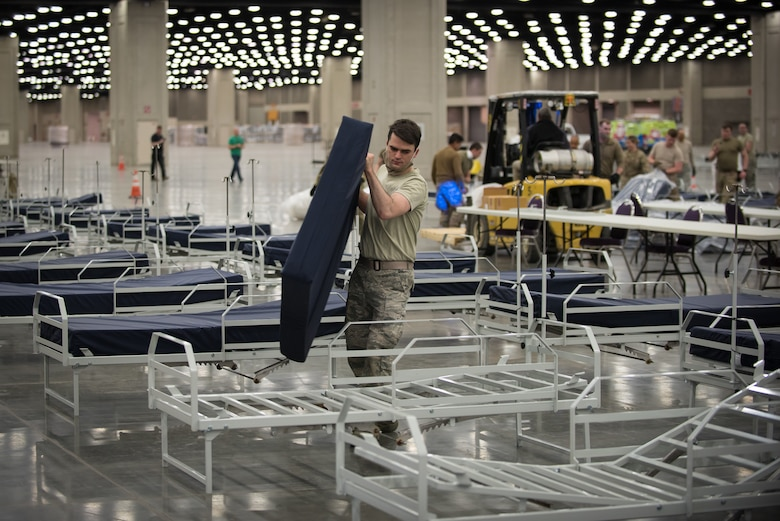 Senior Airman Tristan Baxter of the Kentucky Air National Guard's 123rd Civil Engineer Squadron places a mattress on a hospital bed at the Kentucky Fair and Exposition Center in Louisville, Ky., April 11, 2020. The site, which is expected to be operational April 15, will serve as an Alternate Care Facility for patients suffering from COVID-19 if area hospitals exceed available capacity. The location initially can treat up to 288 patients and is scalable to 2,000 beds. (U.S. Air National Guard photo by Dale Greer)