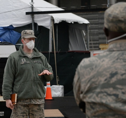 1st Lt. Shawn Lavin of Amherst, N.Y., the commander of the  New York Air National Guard's 107th Attack Wing Fatality Search and Recovery Team, gives a morning briefing outside Bellevue Hospital in New York City, April 4, 2020. The New York National Guard members are supporting the Office of the Chief Medical Examiner to locate and conduct dignified retrieval of remains.