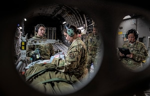 Air Force Reserve Aeromedical Evacuation personnel check on a simulated patient.