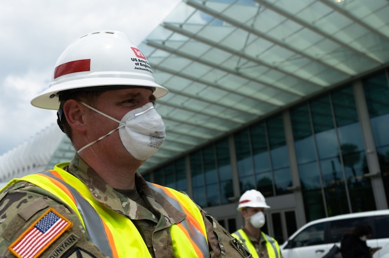 U.S. Army Corps of Engineers, Jacksonville, District deputy commander and senior project manager for the COVID-19 emergency response, Lt. Col. Todd Polk watches as leadership from the City of Miami Beach, the State of Florida and the Chief Engineer of the U.S. Army Corps of Engineers Lt. Gen. Todd Semonite brief the press and the people of South Florida on the current outlook of the COVID-19 Pandemic and the work being done at the Miami Beach Convention Center to convert it to an alternate care facility. USACE staff awarded a construction contract Monday for $22.5 Million to Robins & Morton of Miami, Fla. to convert the Miami Beach Convention Center into a 450-bed hospital. During emergencies, USACE is the federal government's lead public works and engineering support agency. Given its extensive work in building medical facilities for its military stakeholders, it is uniquely qualified to tackle this engineering challenge.