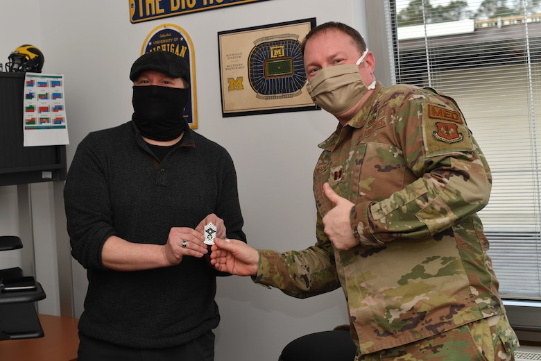Two Airmen holding a coin pose for a photo in an office.