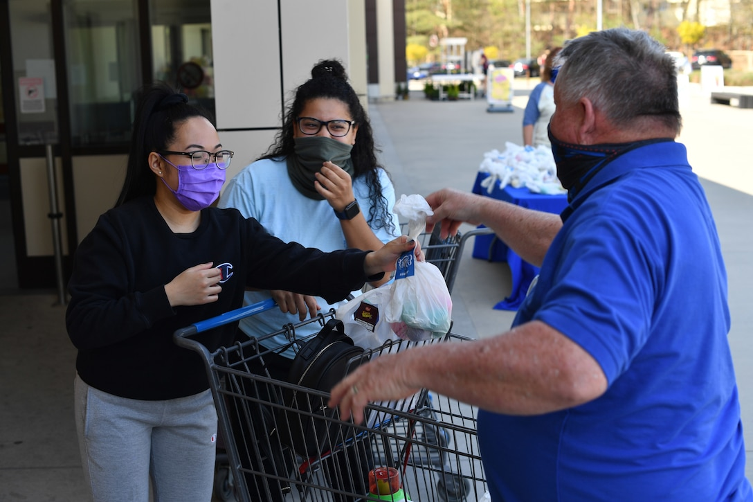 An individual hands an Easter bag to two shoppers leaving the commissary.