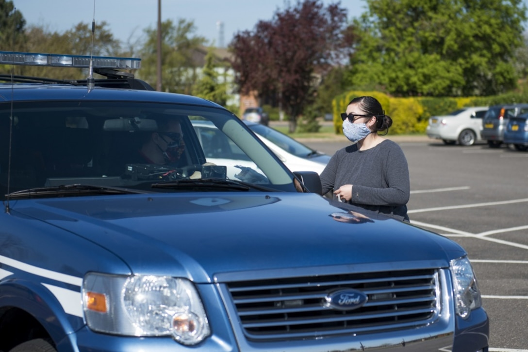 Kristin Joy, a volunteer, hands a cloth face mask at a drive thru at RAF Alconbury, England, April 15, 2020. Volunteers made 232 cloth face masks, which were given to community members to prevent the spread of COVID-19. (U.S. Air Force photo by Airman 1st Class Jennifer Zima)