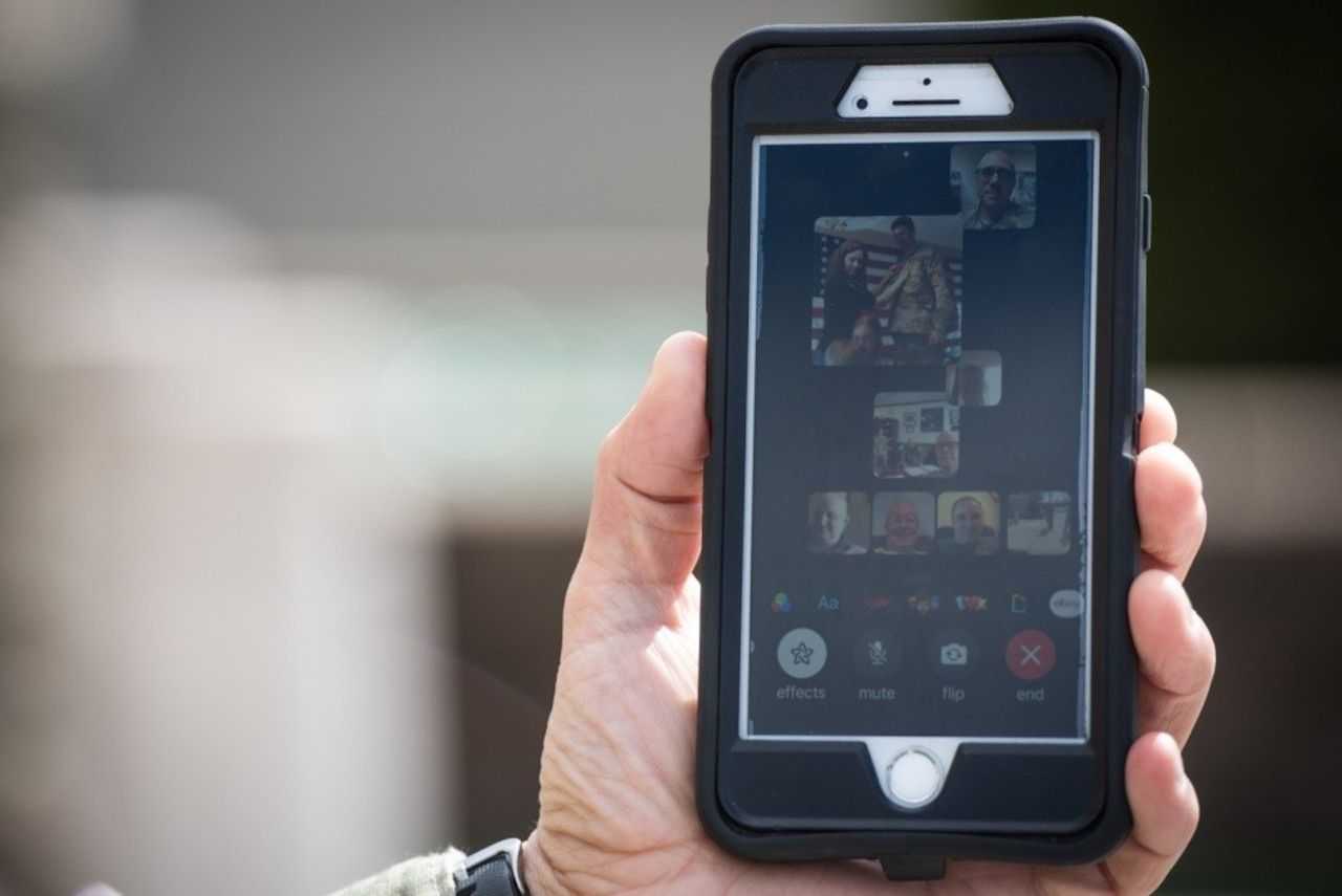 A cellphone is held in the hand showing the screen with communications icons and pictures.