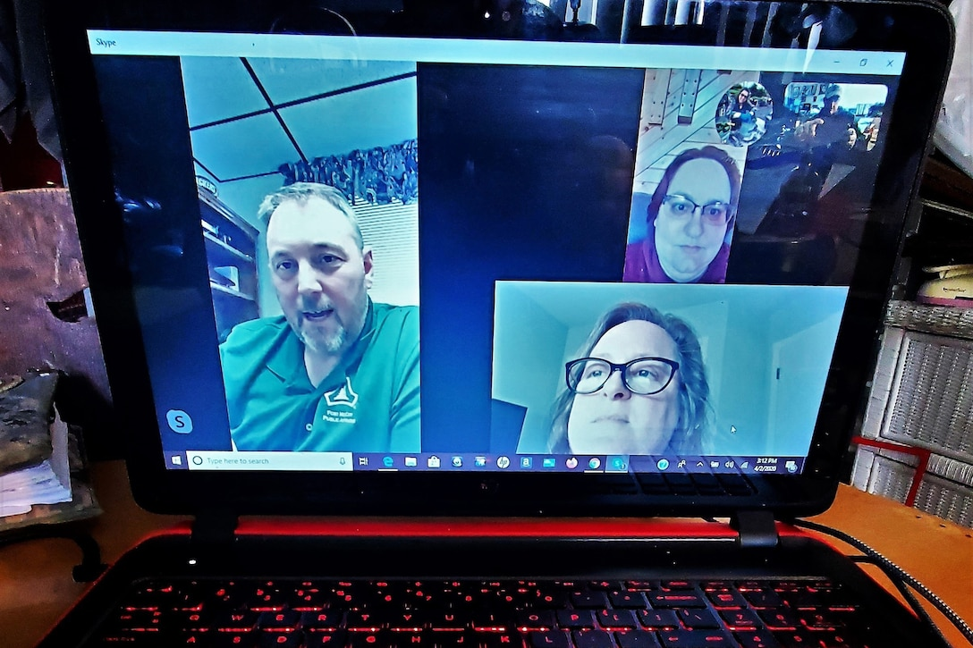A screenshot shows the faces of people on a teleconference.