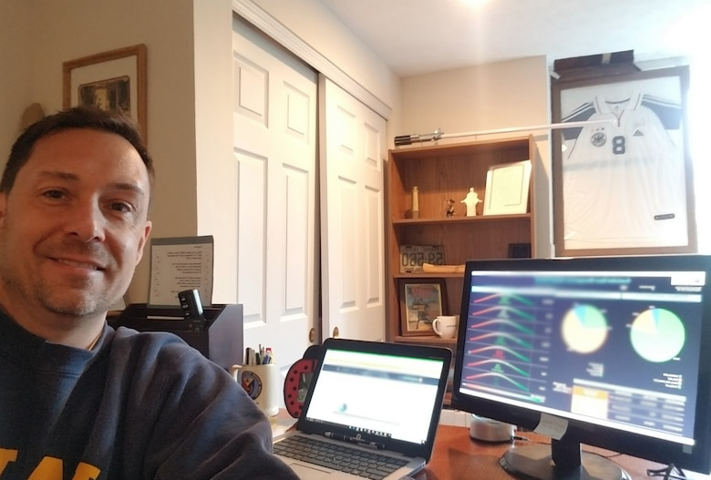 Air Force Installation Contracting Center's Chris Hoff, facilities and construction category management advisor, takes a break from reviewing data in custodial service dashboard in his basement office.