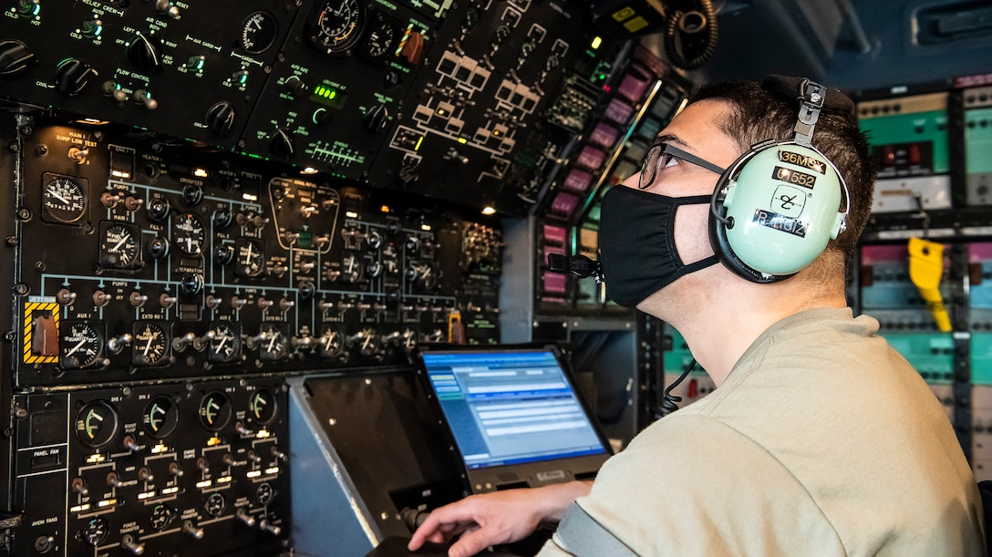 Senior Airman Raynard Ruiz-Sepulveda, 436th Maintenance Squadron C-5 regional isochronal journeyman, operates auxiliary power units April 8, 2020, at Dover Air Force Base, Delaware. Ruiz-Sepulveda monitors APUs and fuel gauges to ensure the C-5 is running properly while being worked on by maintenance and electrical personnel. Despite the threat of COVID-19, Dover AFB Airmen continue to support heavy airlift operations while observing safety precautions such as wearing cloth masks, social distancing, and washing or sanitizing hands frequently. (U.S. Air Force photo by Senior Airman Christopher Quail)