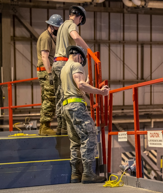436th Maintenance Squadron aircraft maintenance personnel place guardrails along the edges of the stands in the Isochronal Inspection Dock on Dover Air Force Base, Delaware, April 9, 2020. Maintenance personnel wear cloth masks and try to maintain social distance from one another to mitigate the spread of COVID-19 while performing their duties. (U.S. Air Force photo by Senior Airman Christopher Quail)
