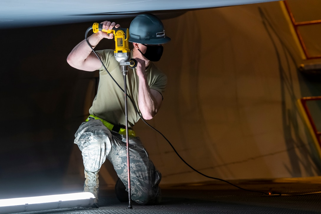 Airman 1st Class Robert Moody, 436th Maintenance Squadron C-5 regional isochronal apprentice, uses a stand-up drill to place stands close to the side of a C-5 Super Galaxy engine at Dover Air Force Base, Delaware, April 9, 2020.  Moody wears a cloth mask  in accordance with Department of Defense instruction to mitigate the spread of COVID-19. (U.S. Air Force photo by Senior Airman Christopher Quail)