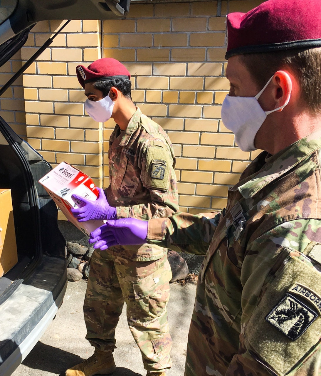 Two uniformed service members wearing face masks and gloves unload medical gear from the back of a vehicle.