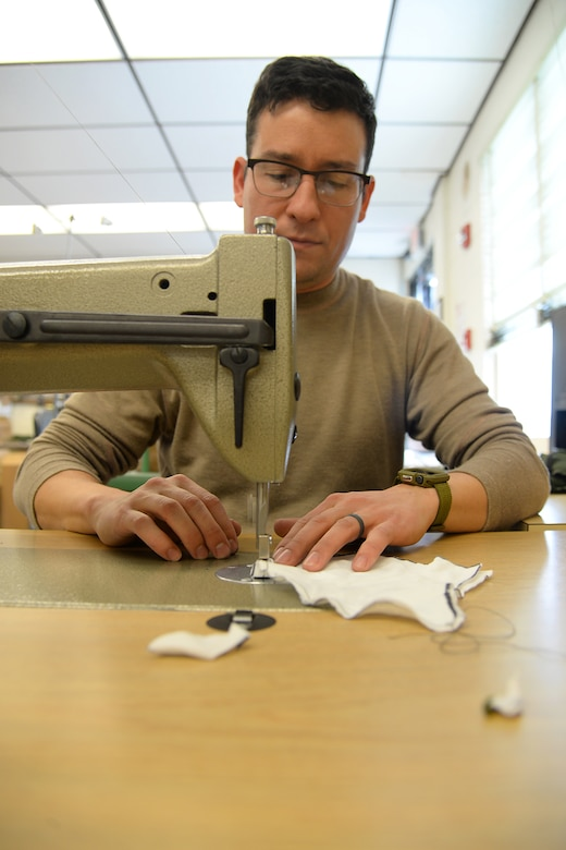 A picture of U.S. Air Force Master Sgt. Kyle P. Brier, an Aircrew Flight Equipment craftsman, sewing face masks.