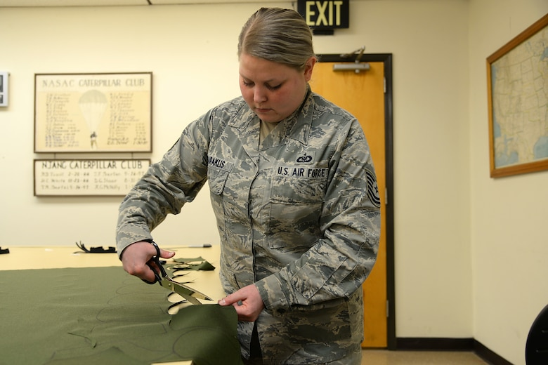 A picture of U.S. Air Force Tech. Sgt. Ashley N. Daraklis, an aviation resource manager, volunteering to prepare fabric for face masks.