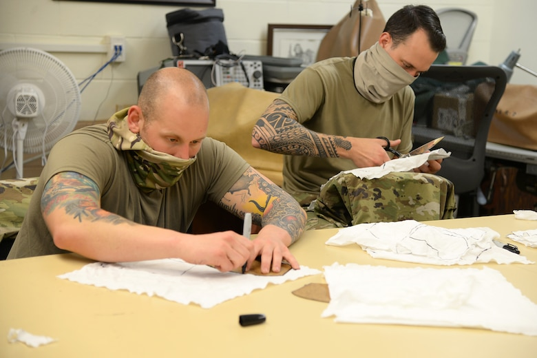 U.S. Air Force Senior Airman Michael R. Ottaviano and Staff Sgt. Brandon M. Staines, aircraft ordinance maintenance technology (Egress) technicians, volunteering to prepare fabric for face masks