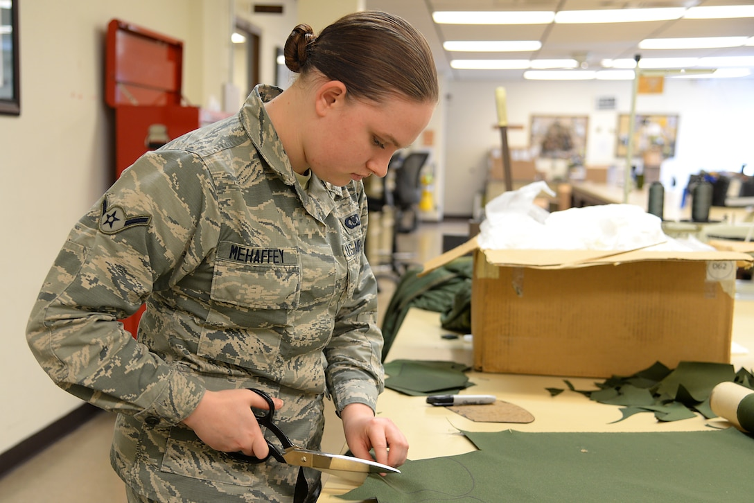 A picture of U.S. Air Force Airman Makayla P. Mehaffey, an aviation resource manager, volunteering to prepare fabric for face masks