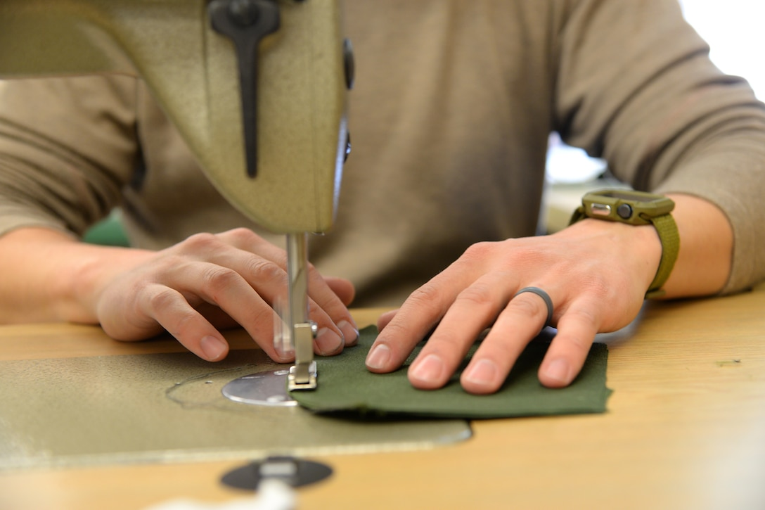 A picture of U.S. Air Force Master Sgt. Kyle P. Brier sewing face masks.