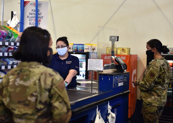 Customers at the Base Exchange on Goodfellow Air Force Base, Texas use proper social distancing and cash out methods while buying their supplies on April 16, 2020. The Exchange has installed plastic shields at all of their register locations to prevent the spread of COVID-19. (U.S. Air Force photo by Senior Airman Seraiah Wolf)