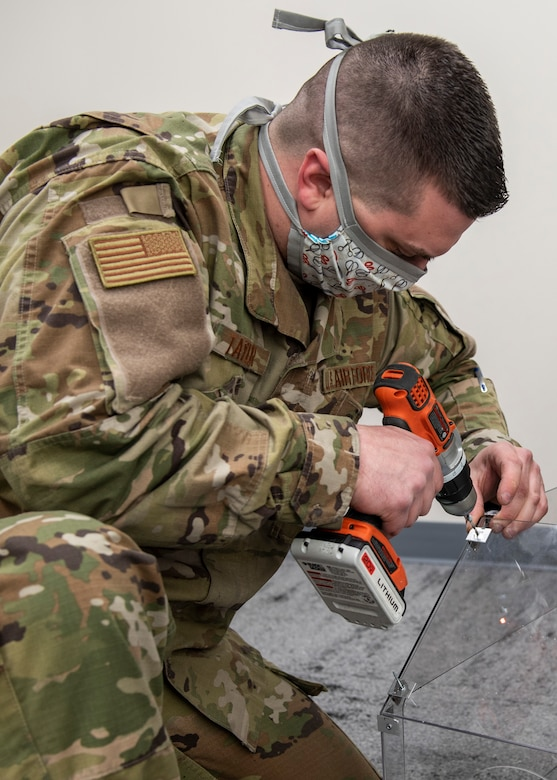 U.S. Air Force Staff Sgt. Andrew Taylor, 673d Medical Support Squadron medical logistics noncommissioned officer in charge of acquisitions, drills a hole in a plastic polycarbonate enclosure at Joint Base Elmendorf-Richardson, Alaska, April 7, 2020. Taylor and U.S. Air Force Senior Airman Michael Shoemaker, 673d Medical Support Squadron biomedical equipment technician, designed and built the reusable device to be a protective barrier between medical providers and a patient to prevent possible exposure to COVID-19 and other airborne diseases. The enclosure can be placed over a patient's head and upper torso prior to intubation or similar treatments, with access to the patient via two holes at the head of the enclosure for a physician's hands and arms, and two side doors for additional access.