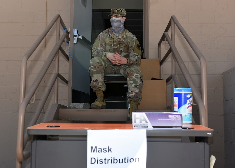 A photo of a U.S. Airman sitting on doorsteps waiting to distribute cloth masks