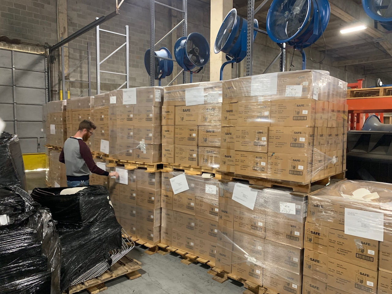 A man in a warehouse scans boxes on pallets.