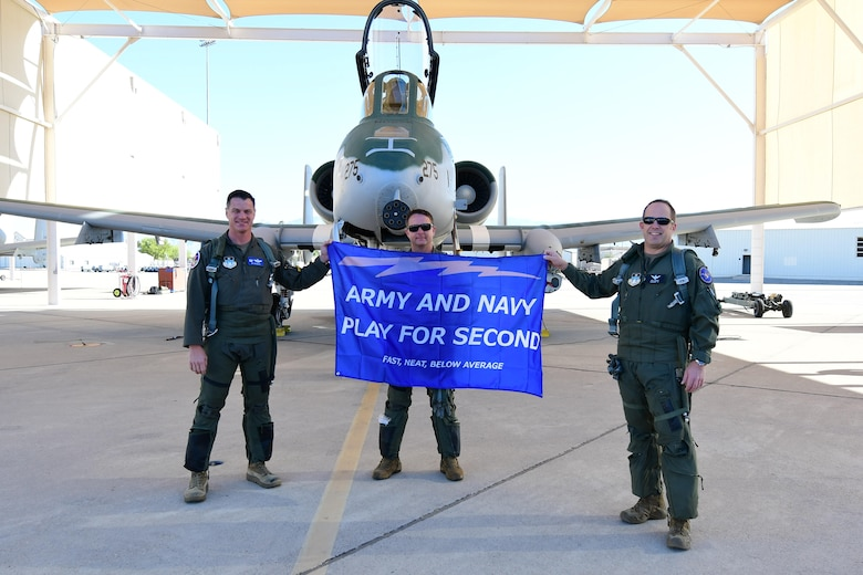 A photo of Airmen posing with a flag