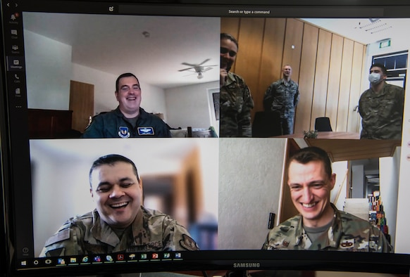 A computer monitor with four split screens shows six Airmen speaking to each other via teleconference video call.