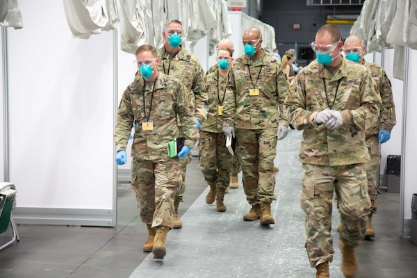 Six soldiers wearing blue face masks walk through the patient care area of an alternate care facility set up as part of the COVID-19 pandemic response.