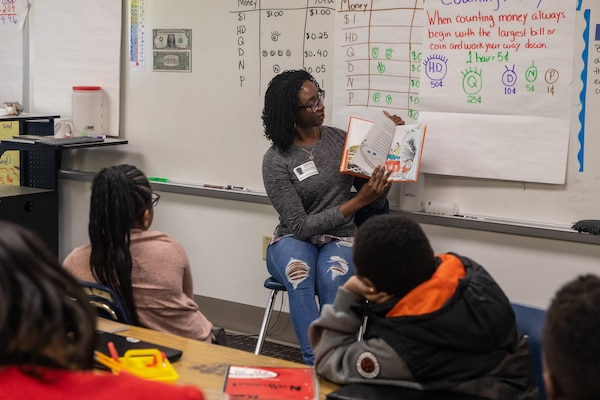 Norfolk Naval Shipyard employee Sandra Demetrius shares a favorite story from her childhood during Read Across America Day at James Hurst Elementary School Mar. 2.